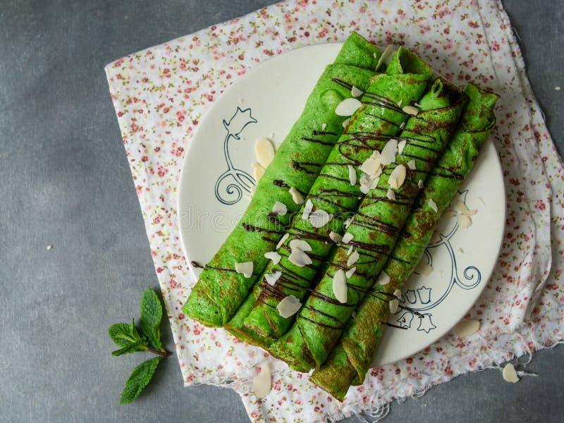 Acuñe los crespones finos del color verde, torcidos en los tubos, con los pétalos de la salsa de chocolate y de la almendra en un fotos de archivo libres de regalías