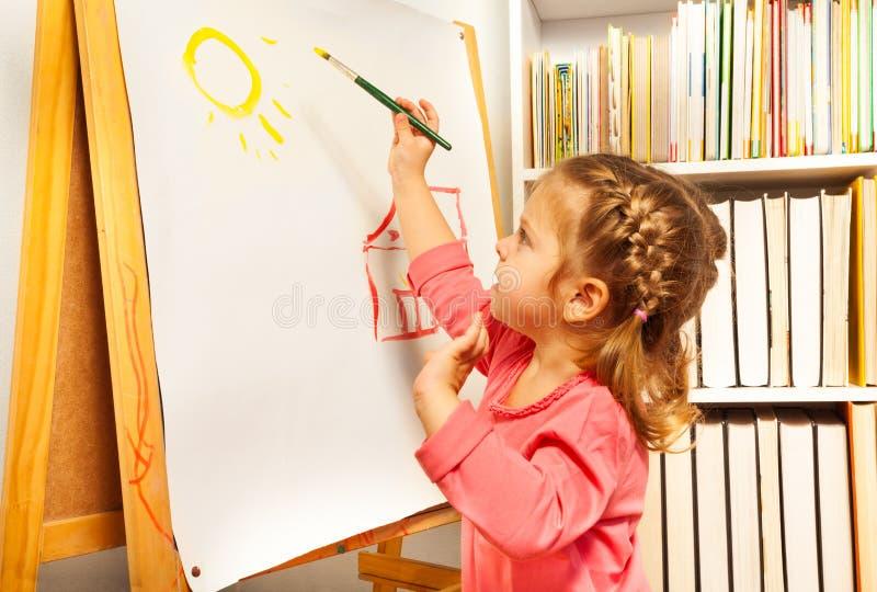 Acuarelas lindas del cepillo de pintura de la muchacha en un caballete fotografía de archivo libre de regalías