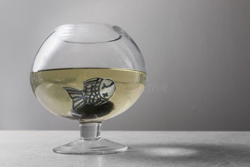 Acuario con los pescados sucios del agua y del papel en la tabla gris foto de archivo libre de regalías