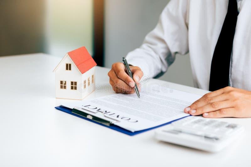 Acuerdo de contrato de firma del papel del hombre asiático para la casa con el hogar modelo imagen de archivo libre de regalías