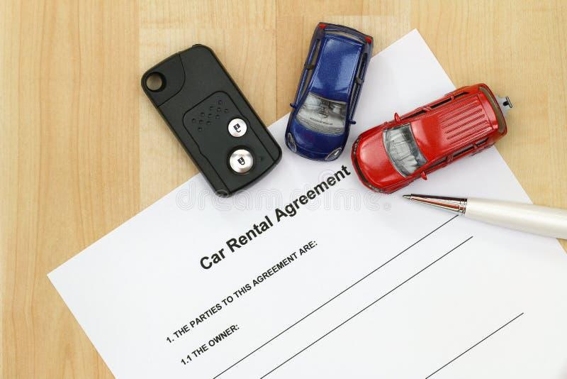 Acuerdo del alquiler de coches, llave remota del coche, una pluma y mini modelos del coche imagen de archivo