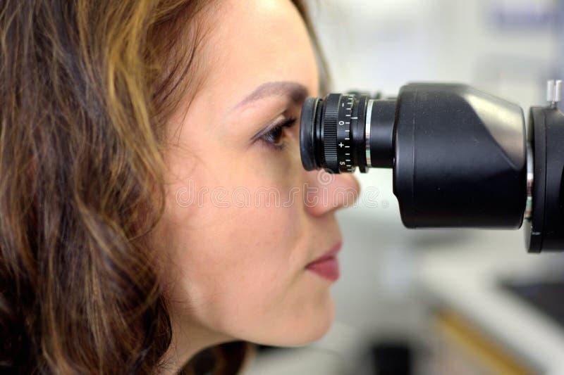 Acuit? visiva dei giovani della donna dell'oftalmologo dell'optometrista examins graziosi dell'ottico di un paziente, fotografie stock libere da diritti