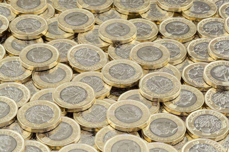 Acumulación del dinero Pila dispersada de monedas de libra británica imagen de archivo