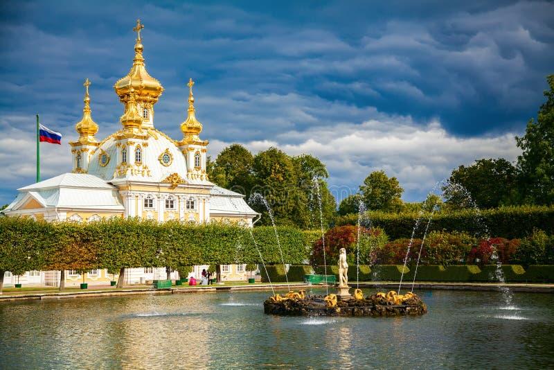 Acumule con la fuente delante de la iglesia del palacio en Peterhof imagen de archivo libre de regalías