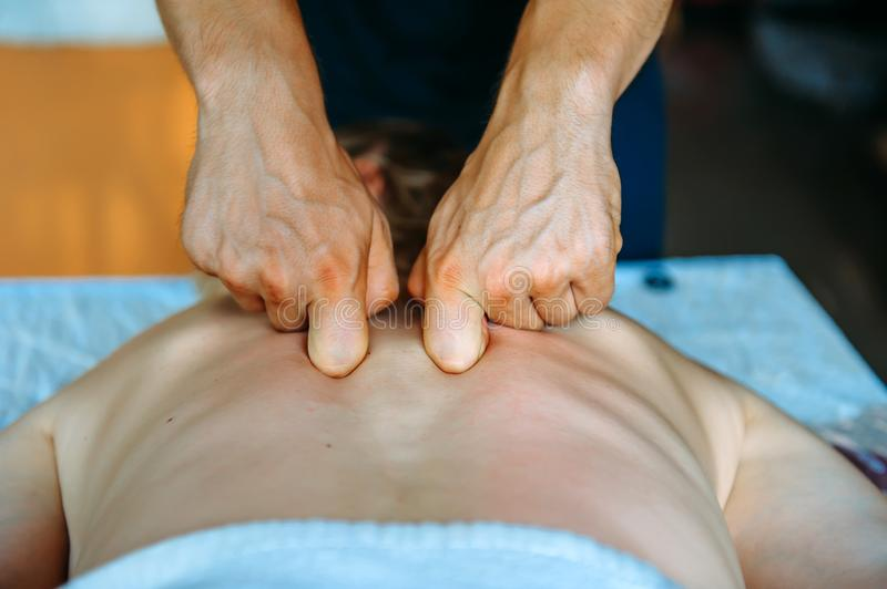 Acupressure massage in spa centre. Woman at acupressure back massage, masseur`s hands close up. Body therapy for healthy lifestyl stock images