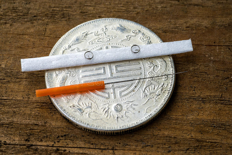 Acupuncture needle on antique chinese coin. With ear needles royalty free stock photo