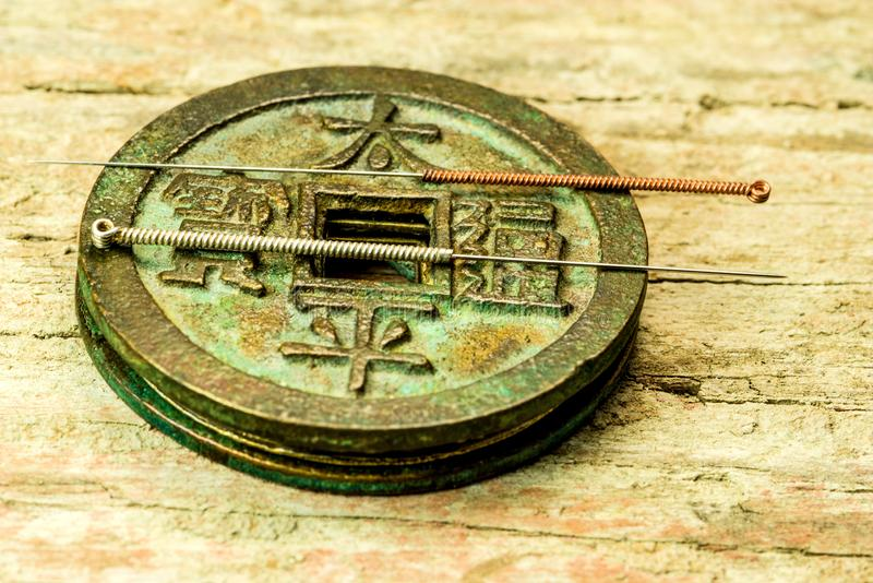 Acupuncture needles on antique Chinese coin. On old plank royalty free stock photos