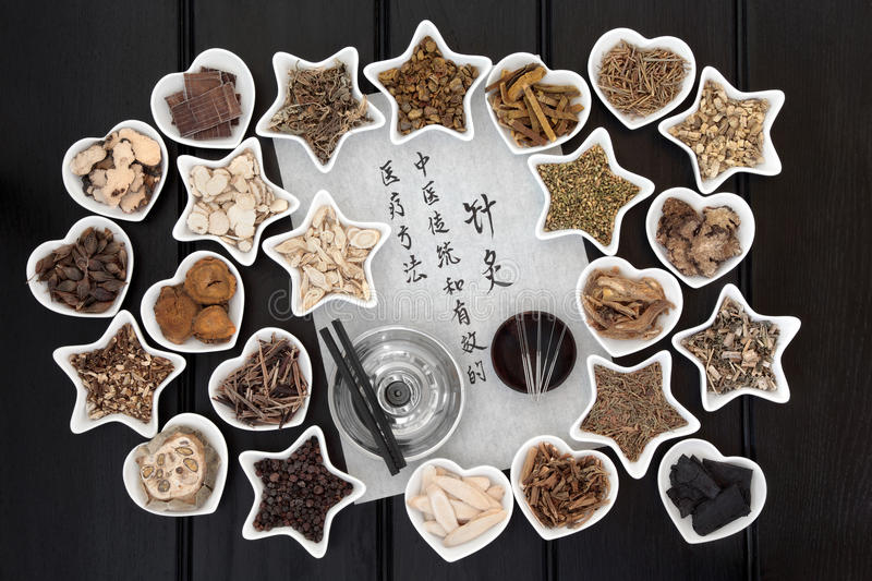 Acupuncture. Needles, chinese herbal medicine selection and moxa sticks with calligraphy script. Translation reads as  chinese medicine is a traditional and royalty free stock photo