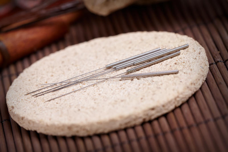 Acupuncture needles on the stone mat royalty free stock image