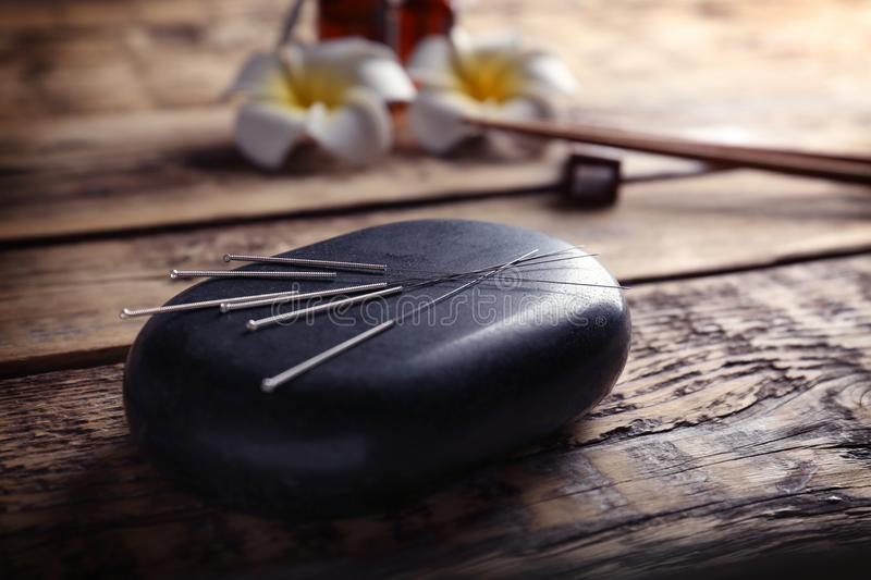 Acupuncture needles with stone. On wooden background stock images
