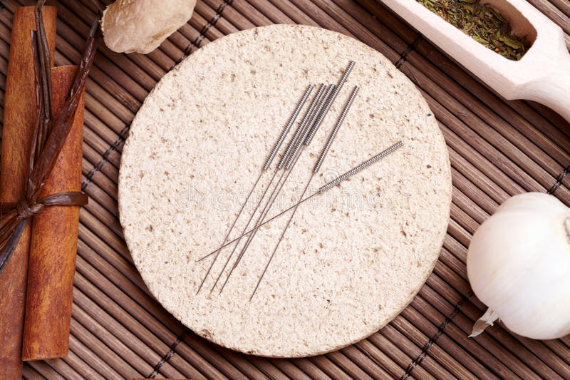 Acupuncture needles and TCM herbs stock photography