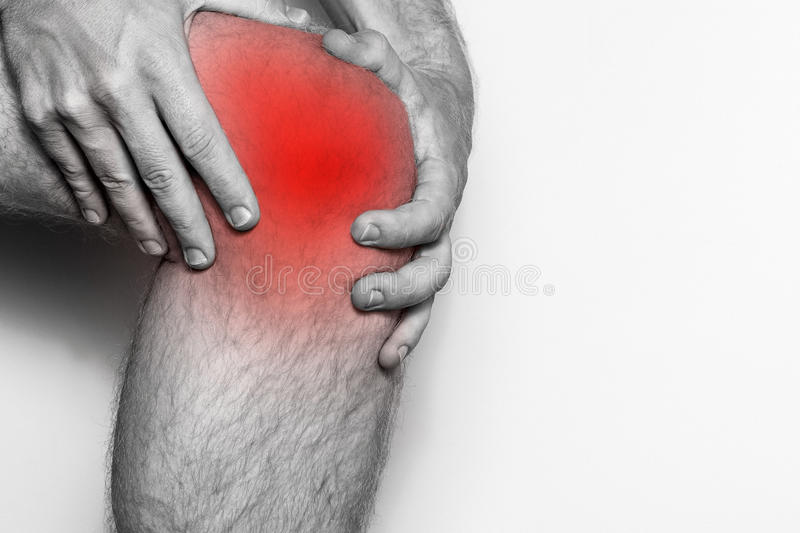 Acute pain in a knee joint, close-up. Monochrome image, on a white background. Pain area of red color royalty free stock photos