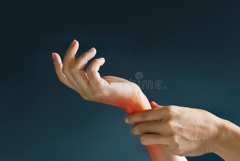 Acute pain in a woman wrist, colored in red on dark blue background. Health issues problems stock image