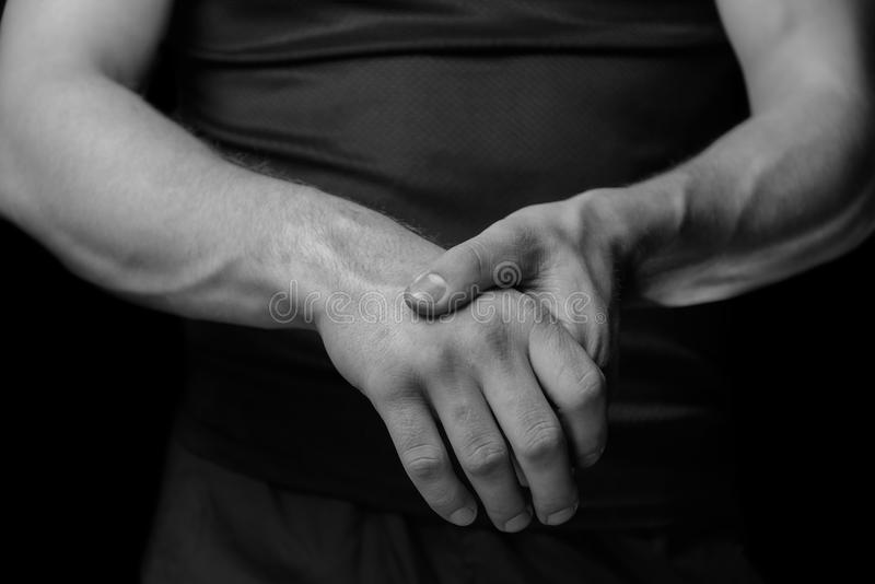 Acute pain in a wrist. Pain in a male wrist. Man holds his hand, monochrome image royalty free stock images