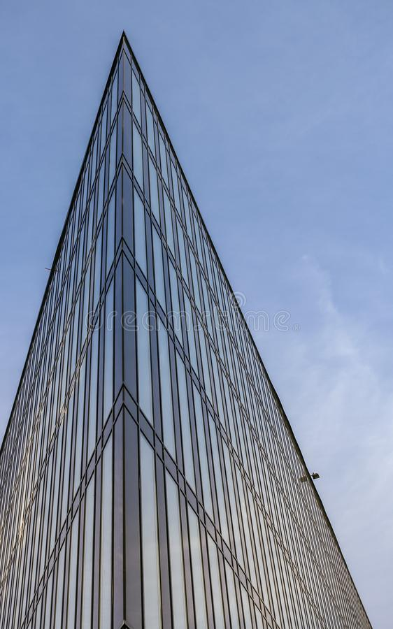 An acute part of a modern building directed upward to the blue sky. An acute part of a modern building made of glass and concrete, directed upward to the blue royalty free stock photography
