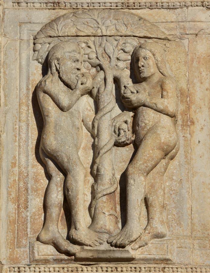 Adán y Eva comen la fruta del árbol prohibido fotos de archivo