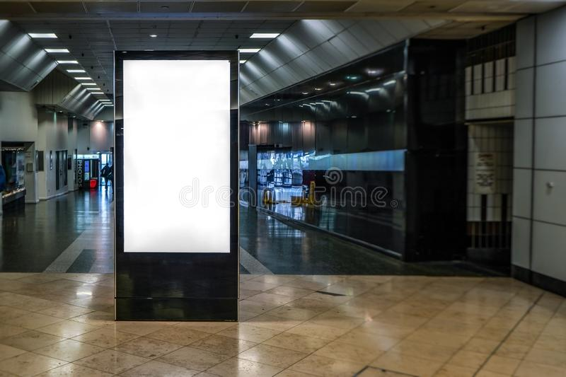 Ad screen mock up at small shopping centre, dark corridor leading outside in background stock image