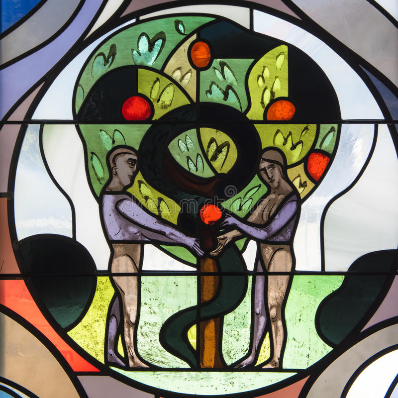 Adam and Eve. Adam gives Eve the forbidden apple. Illustration on stained glass in St. Jodokus Church in Immenstaad, Germany royalty free stock images
