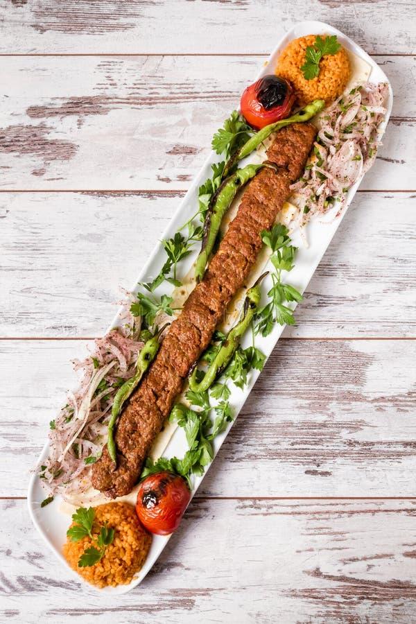 Adana Kebab Słuzyć z Zielonymi warzywami w bielu talerzu fotografia royalty free