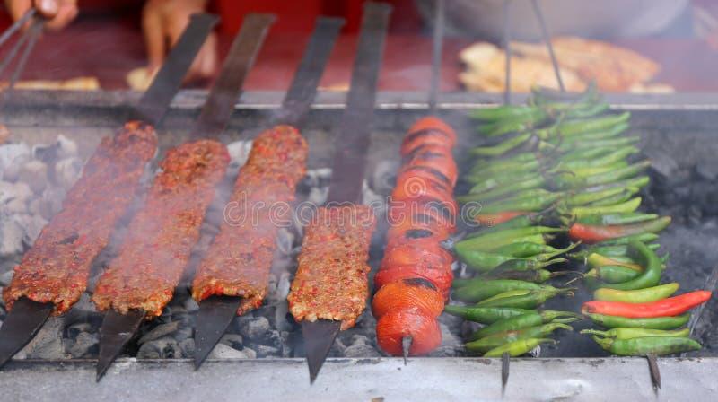 Adana Kebabs kucharstwo z pomidorami i Zieleni pieprze na węglu drzewnym piec na grillu obrazy stock