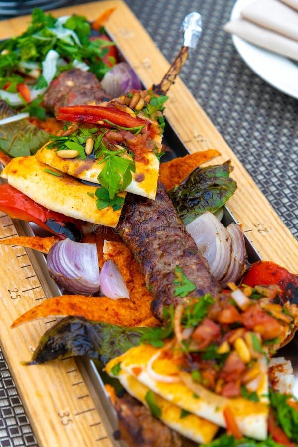 Adana-no espeto com vegetais e pão do pão árabe - prato turco tradicional foto de stock