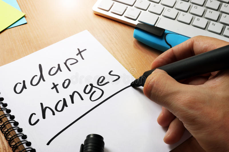 Adapt to changes. Adapt to changes written in a note royalty free stock photography
