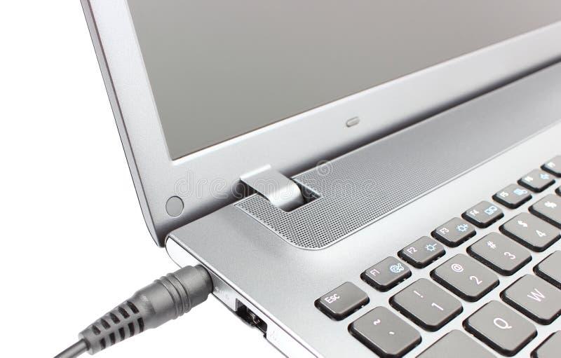 Adaptador de enchufe que es conectado con el ordenador portátil imagen de archivo libre de regalías