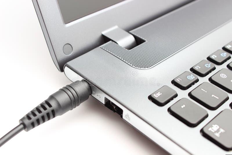 Adaptador de enchufe que es conectado con el ordenador portátil foto de archivo