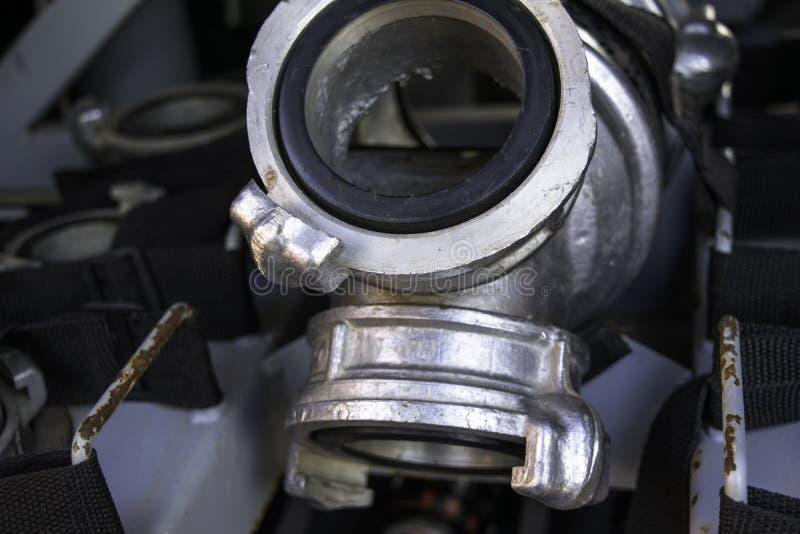 Adaptadores do coletor e do fogo da água do fogo situados nas montagens em um compartimento do veículo do fogo Dispositivo do ada imagens de stock