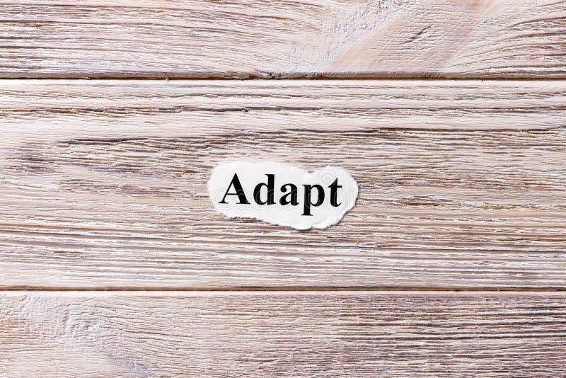 Adaptez du mot sur le papier Concept Les mots de s'adaptent sur un fond en bois images stock