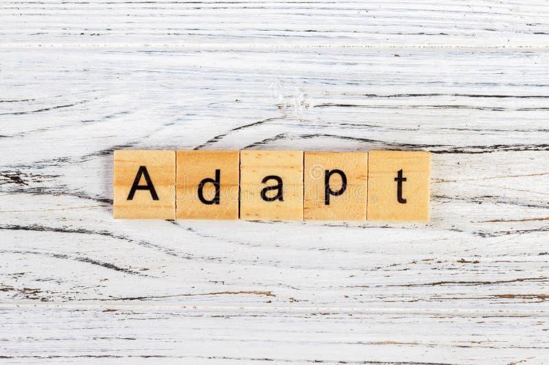 ADAPTEZ Word écrit dans le concept en bois de cube photo libre de droits