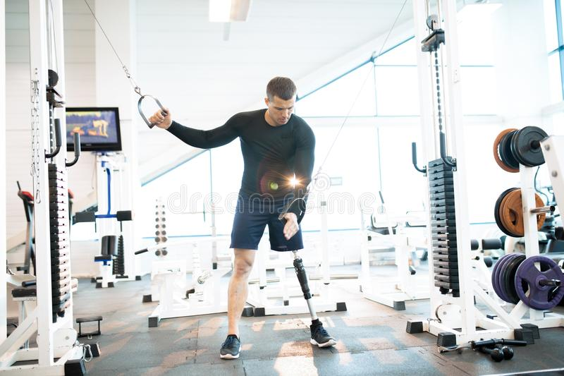 Adaptive Athlete Using Exercise Machines in Gym stock photo