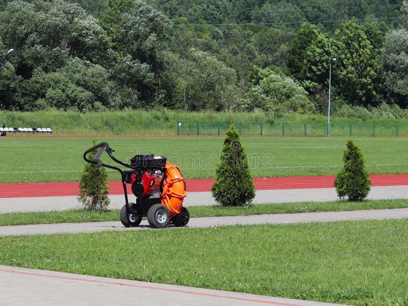 Adattamenti per la cura dei prati inglesi dei campi di football americano e dello stadio Una macchina che facilita il lavoro manu fotografia stock
