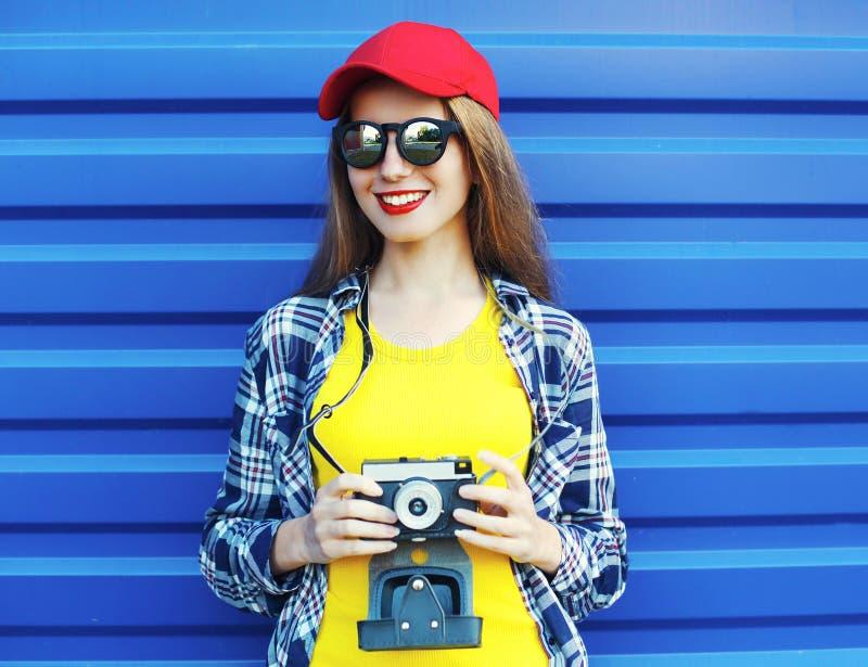 Adatti ad uso abbastanza sorridente della ragazza i vestiti variopinti con la retro macchina fotografica sopra il blu immagine stock libera da diritti