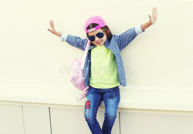 Adatti ad uso del bambino della bambina gli occhiali da sole ed il berretto da baseball in città sopra bianco fotografie stock libere da diritti