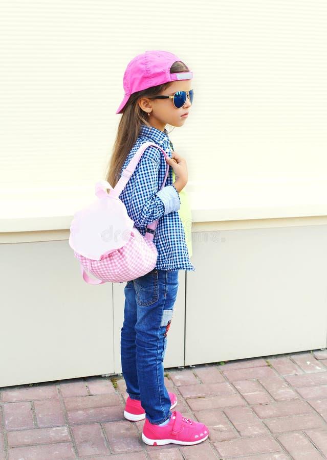 Adatti ad uso del bambino della bambina gli occhiali da sole, il berretto da baseball e lo zaino stanti nel profilo sopra bianco immagini stock libere da diritti