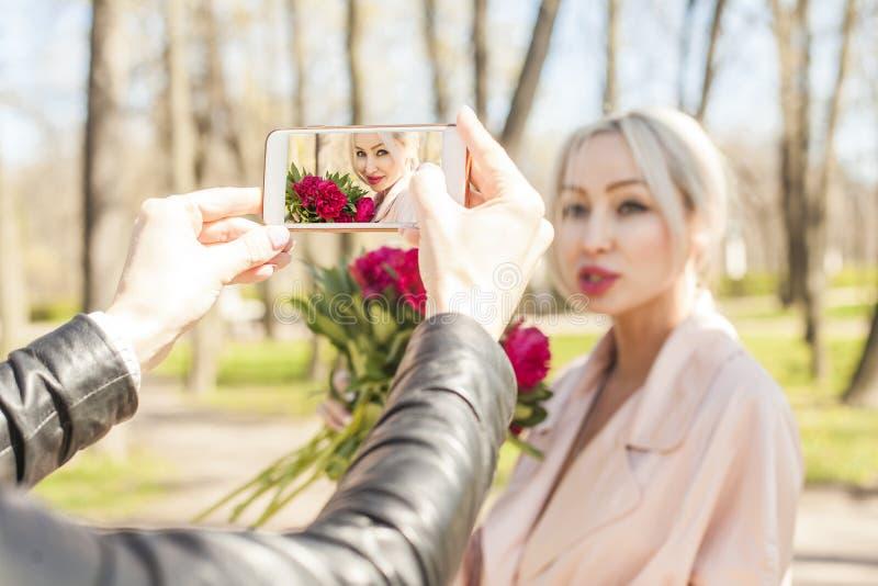 Adatti all'aperto il ritratto con i fiori rossi su Smartphone fotografie stock libere da diritti