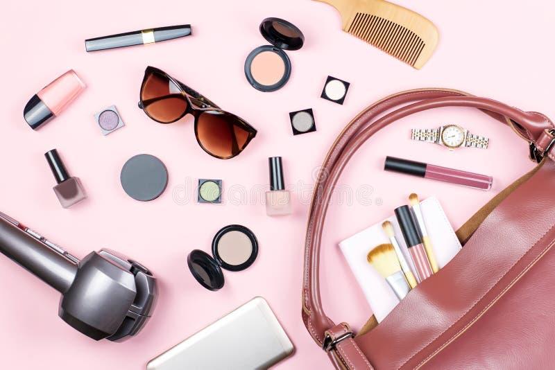 Adatti a donna la disposizione piana femminile con i prodotti e gli accessori di bellezza su fondo rosa fotografia stock libera da diritti