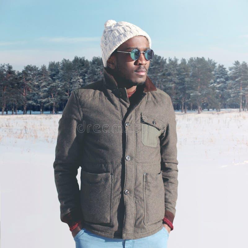 Adatti a giovane uso africano alla moda dell'uomo gli occhiali da sole ed il rivestimento con il cappello tricottato nell'inverno immagine stock libera da diritti