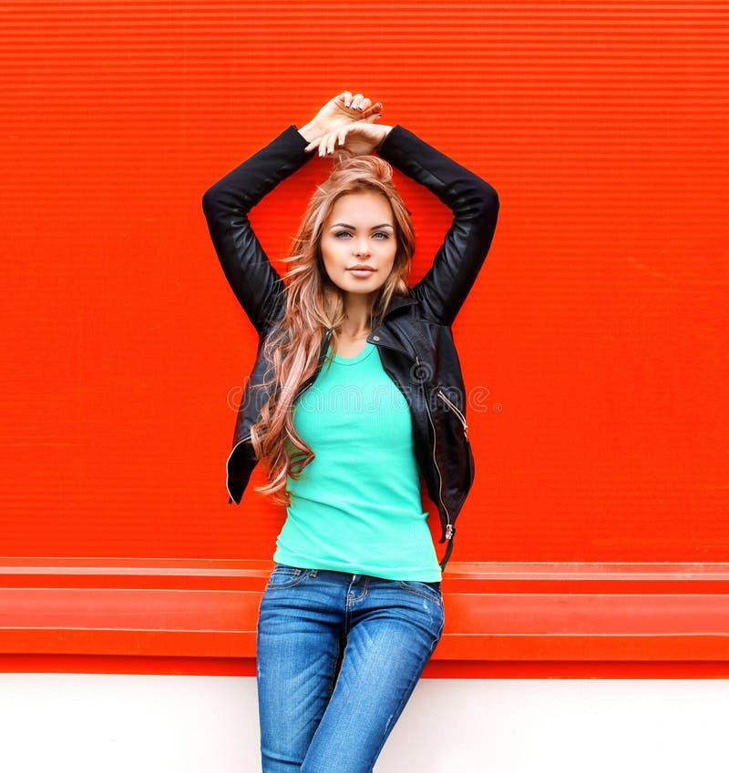 Adatti il bello giovane modello biondo della donna nello stile nero della roccia sopra rosso variopinto immagine stock libera da diritti