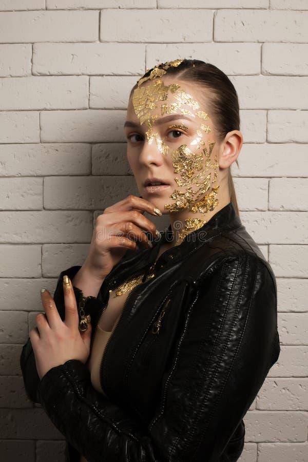 Adatti il colpo della donna castana elegante con la stagnola di oro sul suo fac immagine stock