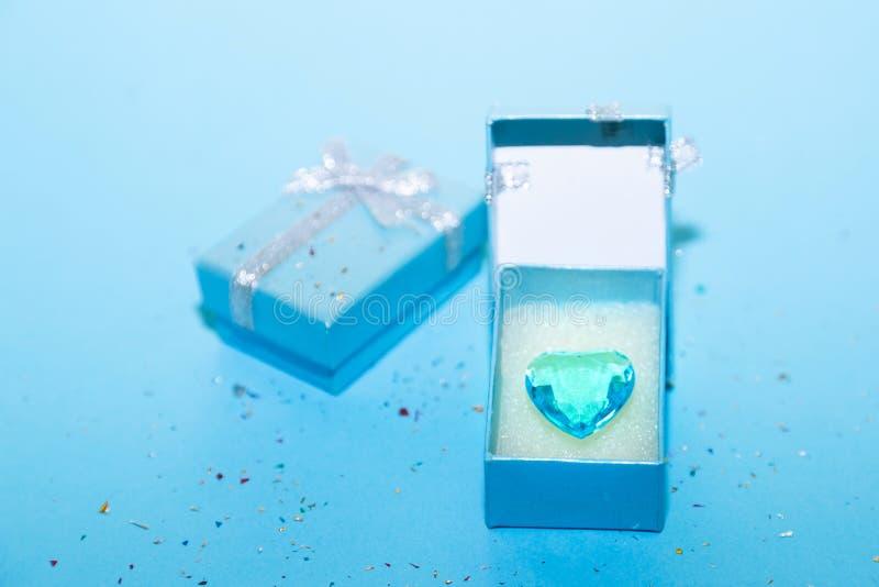 Adatti il fondo blu con il regalo o contenitore di regalo, cuore e vista superiore degli zecchini immagini stock