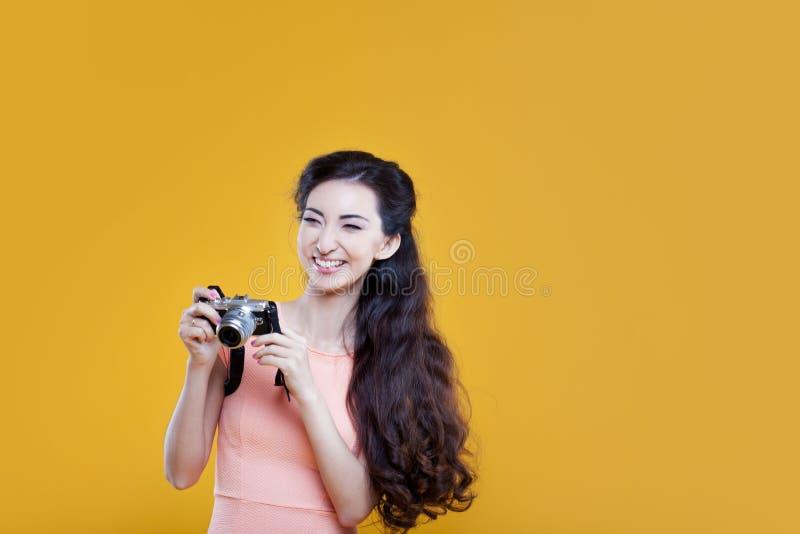Adatti il fotografo asiatico della ragazza con la macchina fotografica, ritratto su fondo giallo fotografia stock libera da diritti