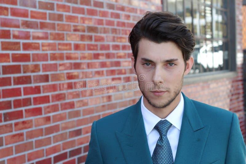 Adatti il giovane uomo d'affari che indossa il vestito verde legame classico su fondo rosso fotografia stock