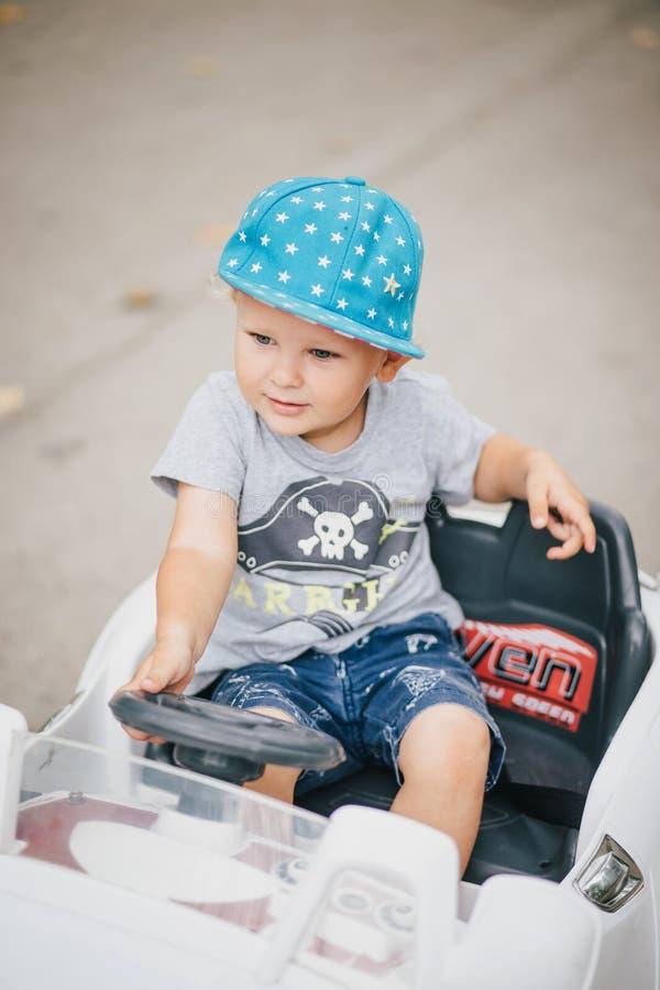 Adatti il ragazzino che conduce l'automobile del giocattolo in un parco fotografia stock libera da diritti