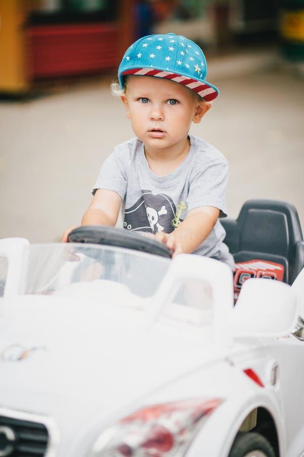 Adatti il ragazzino che conduce l'automobile del giocattolo in un parco immagini stock libere da diritti