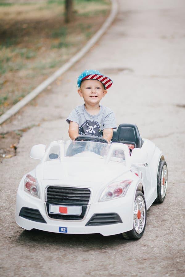 Adatti il ragazzino che conduce l'automobile del giocattolo in un parco fotografie stock libere da diritti