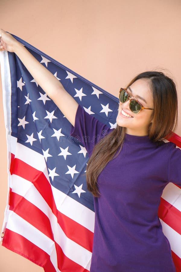 Adatti il ritratto degli occhiali da sole d'uso della donna asiatica dei pantaloni a vita bassa fotografia stock