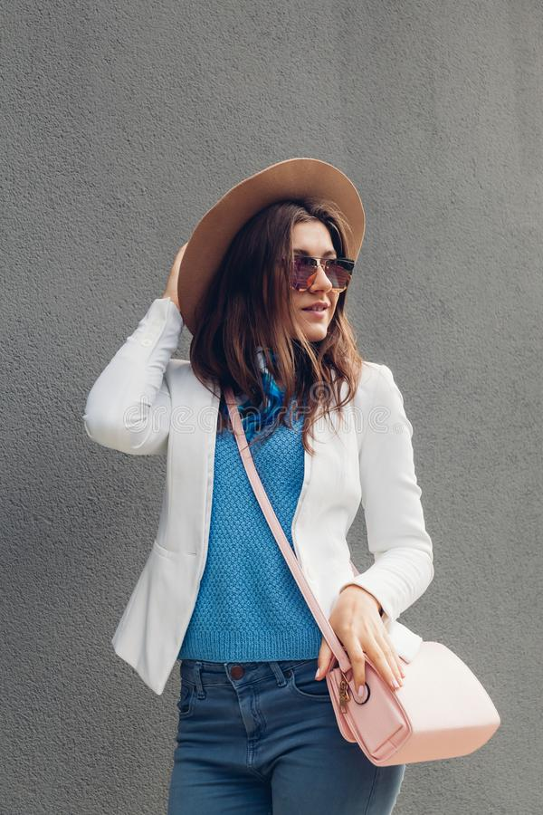 Adatti il ritratto del rivestimento d'uso della giovane donna graziosa, il cappello, occhiali da sole e borsa di tenuta sopra fon immagini stock