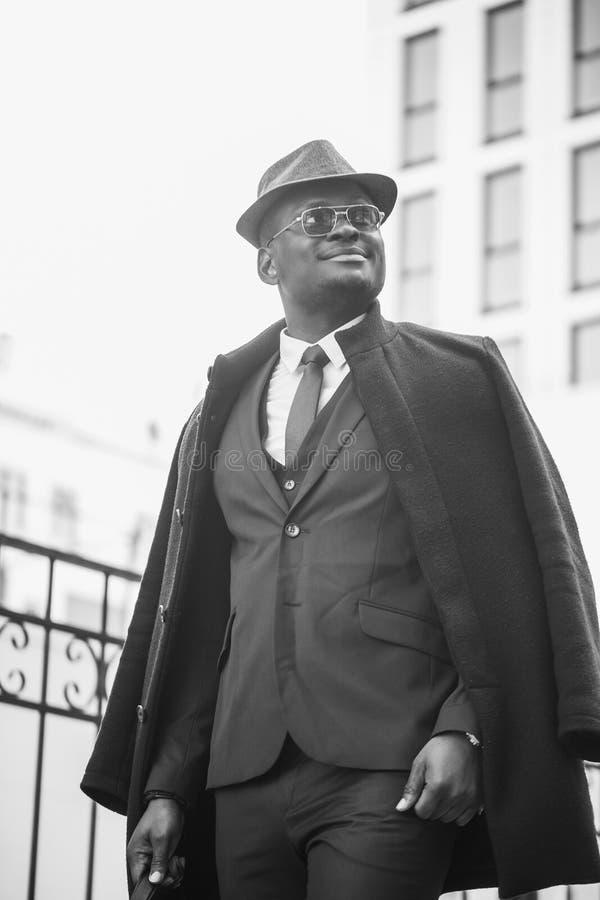 Adatti il ritratto dell'uomo dell'africano nero che cammina sulla via con una borsa fotografia stock